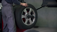 Stock Video Footage of Auto mechanic is checking the precision of tires