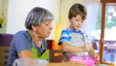 Elder woman having fun cooking with beautiful child Stock Footage