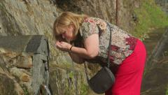 Woman drinking from mineral spring, furnas, san miguel, azores Stock Footage