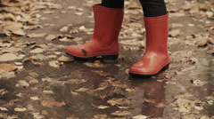 Child with rubber boots jumping into puddle Stock Footage