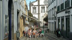 Tourists sit at cafe, cathedral, ponta delgada, san miguel island, azores Stock Footage