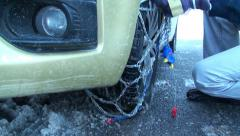 Fitting snow chains on car wheel 1 - stock footage