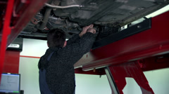 Auto mechanic fixing the lower part of the chassis - stock footage