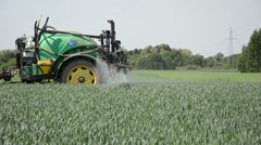 tractor pulls tank with fertilizer from the sprinkler spray crop - stock footage