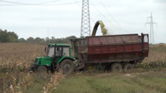 Harvester ride close to tractor and pour grain into the trailer Stock Footage