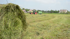 Closeup of hay bale and blurred machine tractor collect straw Stock Footage