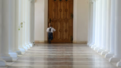 Little boy try to open a big door on long lobby with stone columns - stock footage
