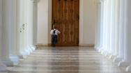 Stock Video Footage of Little boy try to open a big door on long lobby with stone columns