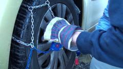 Fitting snow chains on car wheel 2 Stock Footage