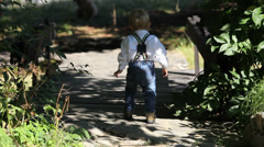 Little boy walk alone on road in nature Stock Footage
