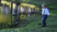 Handsome little boy play on lake shore, have fun, throw the little stones Stock Footage