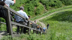 People tourists downstairs from mound hill in park Stock Footage