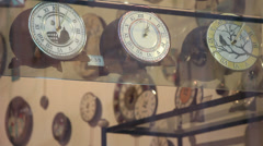 Several ticking clocks in shop window (rack focus) - stock footage