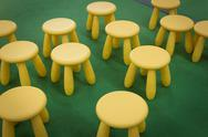 Stock Photo of stools scattered on green floor