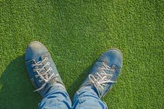 feet in running shoes on the lawn. - stock photo