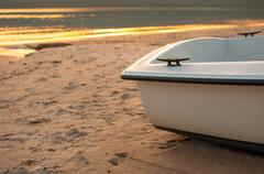 Stern of a boat in the foreground with the distant golden sea at sunset Stock Photos