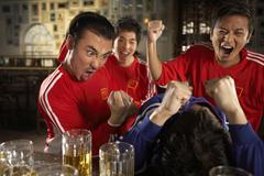 Sports Enthusiasts Competing In Bar Stock Photos