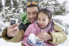 Father And Daughter Taking A Photo Of Themselves On Ski Field Stock Photos