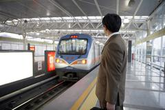 Businessman Waiting For Train To Approach - stock photo