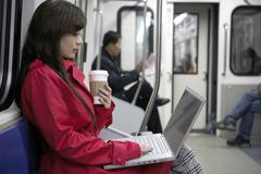 Woman Sitting On Train Typing On Laptop Stock Photos