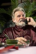 Man Talking On Cellphone At Dinner Table - stock photo