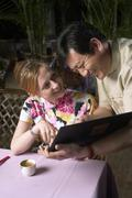 Waiter Helping Woman Order From Menu - stock photo
