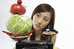 Young Woman With Healthy Food And Pills On Scales - stock photo