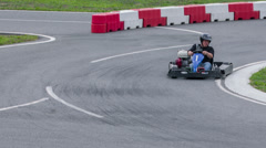 Go-cart racer drives fast across the track Stock Footage