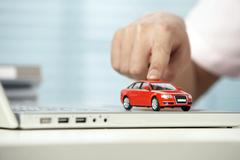 Red Toy Car Being Pushed Along A Computer Keyboard Stock Photos