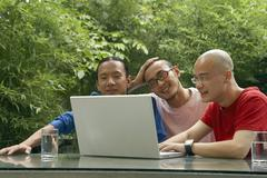 Three Young Men Sitting Outside Watching Laptop Stock Photos
