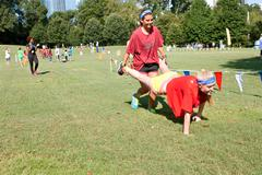 Two young women compete in wheelbarrow race at summer fundraiser Stock Photos