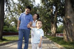 Family Taking A Stroll Through The Park - stock photo