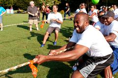 tug-of-war teams pull rope in summer fundraising event - stock photo