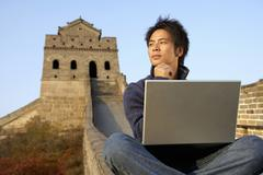 Young Man Uses Laptop On The Great Wall Of China - stock photo