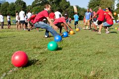 Two teams sprint for balls to begin dodge ball game Stock Photos