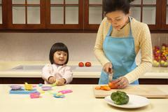 Young girl playing in the kitchen while her mother cooks - stock photo
