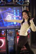 Teenage Girl  On Dancing Game At Arcade - stock photo