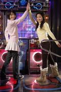 Teenage Girls On Dancing Game At Arcade - stock photo