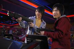 Teenage Boys Playing Shooting Games At Arcade - stock photo