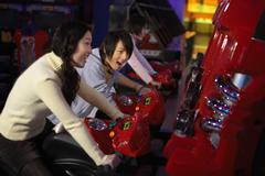 Teenagers Racing Motorbikes At Arcade - stock photo