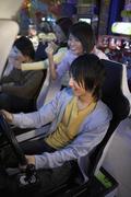 Teenagers Playing Racing Games At Arcade - stock photo