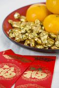 Red Packets Containing Monetary Gifts, With Mandarin Oranges And Sweets - stock photo
