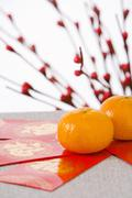 Stock Photo of Red Packets Containing Monetary Gifts With Mandarin Oranges