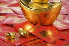 Gold Yuanbao Ingot Symbolizing Wealth And Red Packets Containing Monetary Gifts - stock photo