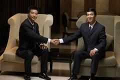 Two business leaders shake hands at an exclusive business club Stock Photos