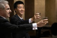 Two business leaders share a toast at an exclusive business club Stock Photos