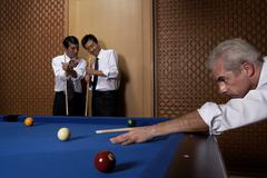 Three professionals play billiards Stock Photos