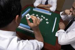 Three businessmen play Mahjong Stock Photos