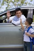 Father dropping son off at school Stock Photos