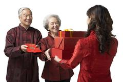 A daughter exchanging gifts with her parents on Chinese New Year Stock Photos